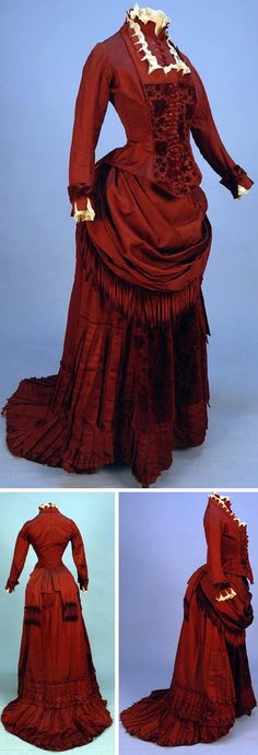 Circa 1880 silk and velvet bustle dress with fringe, claret-colored ottoman with self-piping, lace, and crenelated trim at neck, Bib front and cuff, floral cut velvet bodice, and skirt front panel. Draped skirt trimmed in chenille fringe and pointed pleats, crocheted buttons, and polished cotton lining. Via Whitaker Auctions.