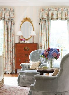 An antique tea table resides between the master bedroom's velvet-covered chairs.