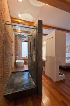 Amazing Studio Apartment. Modern Chic Bathroom with amazing floorplan. Bathroom sink/vanity area is used to create a space to divide the bedroom from the bathroom.Beautiful Shower & bathtub, gorgeous wood flooring & beams & brick wall.