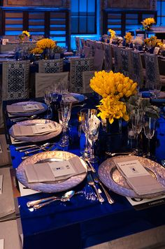 Cobalt blue tables are punctuated with silver plates and bright yellow calla lilies.