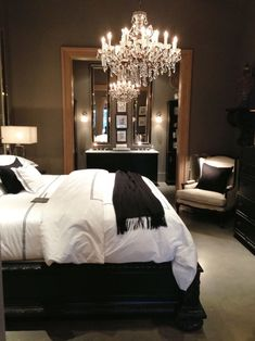 Bedroom with dark walls, white bedspread, dramatic lighting.