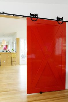 a bright sliding barn door adds a pop