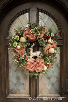 Rustic charm meets Christmas chic with this DIY wreath featuring burlap ribbon, ornaments, berry sprays and greenery.