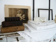 Linens, books, frames and an old photo on a chippy shelf.