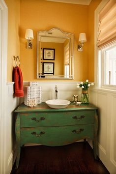 I love the mix of styles you see with this sink vanity. A low vintage dresser is paired with a vessel sink and modern faucet. The result is one eye-catching piece for the bathroom.