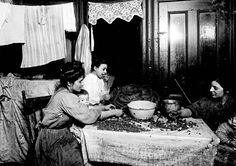 The kitchen served multiple roles in New York tenements in the late 19th and early 20th centuries. Here, members of an immigrant family shell nuts at their kitchen table to earn money.    Read more: http://forward.com/articles/127914/dishing-up-history/#ixzz2LDcLSI74