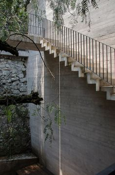 Staircases descend around a courtyard hidden inside this four-storey concrete house