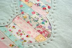 Tiny scraps, strip pieced and laid beneath a design. Gorgeous idea!