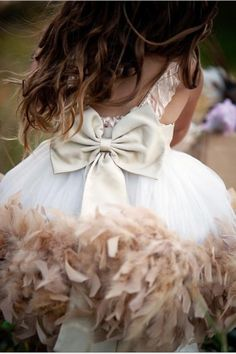 It's all about the details on this dress with a back statement bow and ruffled feather hem