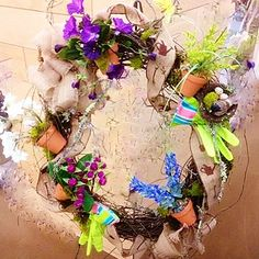 A cute wreath for the gardener. Mini clay pots filled with Spring flowers -you even get the work gloves.