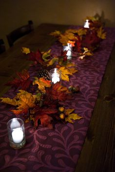 Creative seasonal table decor:  For a classic fall wedding, faux leafs and acorns with bright white candles make an amazing accompaniment to a dark-hued runner.