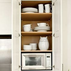 Disappearing Act | Hide utilitarian features by choosing a cabinet with a pullout waste bin and adding an outlet to the back of a cabinet for the microwave. | SouthernLiving.com