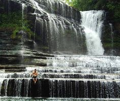 Cummins Falls, Cookeville, TN.  About halfway between Nashville and Knoxville, Cummins Falls cascades 50 feet over wide stair-stepped rocks into a deep cold-water pool. It's a hard-earned scramble to the bottom that involves hiking to the overlook, wading across the ankle-deep stream, climbing up to the ridge, and using a rope guide to walk yourself down to the water. This is not a swimming hole for lightweights.
