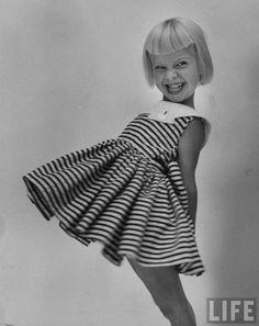 A young model wearing a dress  Photographer: Lisa Larsen  USA, 1953.  © Time Inc. fashion photographer, black and white kids photos, childrens fashion photography, kids fashion, dress, bangs, children photography, stripe, photography kids