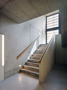 Swiss school fronted by vertical larch battens featuring a concrete staircase.
