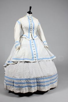 """Sprigged blue and white cotton summer dress, late 1860's, bodice, skirt & over-skirt, trimmed with blue cotton bands and buttons; bust: 32""""- when I look at this, I see a """"remake"""" of an old dress into the new style of the late 1860's."""