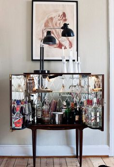Compact home bar furniture cabinet hinges open with mirrored back shelves for entertaining. #homebar #furniture #cabinet