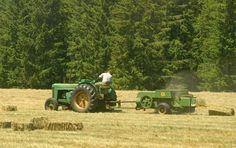 John Deere R baling hay.