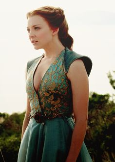Natalie Dormer as Margaery Tyrell in her blue dress with a rose brooch and gold flowery details.