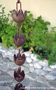 Rain chains are a beautiful and functional alternative to traditional, closed gutter downspouts. Guiding rain water visibly down chains or cups from the roof to the ground, rain chains transform a plain gutter downspout into a pleasing water feature. From the soft tinkling of individual droplets to the soothing rush of white water, they are a treat to listen to.
