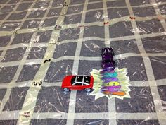 Coordinate graphing with a giant floor graph, toy cars, crashes, and a city