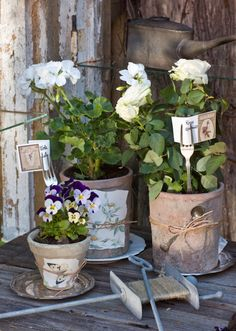 use old silver forks to hold cards in flower pots.