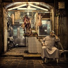 A camel butcher in front right of his shop in the covered souks of Aleppo, Syria.