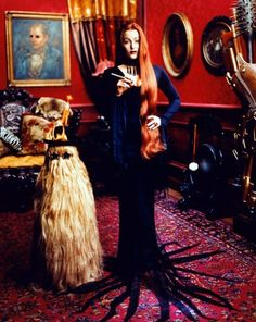 Gillian Anderson as Morticia Addams with Cousin It.