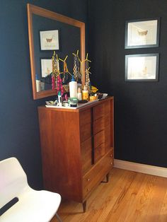 Large mirror on wall behind tall dresser