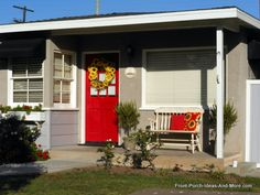Coordinated red front door, pillows, and sunflower theme make great use of this small front porch! Front-Porch-Ideas-and-More.com #porch