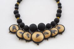 What the Heck? It Goes Around Your Neck! Statement necklace by Betty Nelsen, made from handcrafted polymer with image transfer, glass, rubber-coated acrylic, and resin.