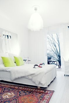 white, with printed rug, and bright pillows