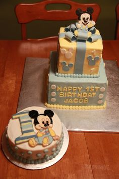 Mickey Mouse 1st birthday cake. Butter cake with vanilla buttercream. Fondant and gumpaste bow, letters, mickey, and mouse ears on the large cake; buttercream transfer Mickey and number on smash cake. smash cakes, 1st bday, baby mickey mouse cakes, 1st birthday cakes, 1st birthday mickey mouse cake, cake boxes, first birthdays, babi mickey, first birthday cakes