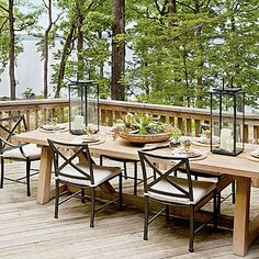 Nature-Inspired Lakeside Table | A wood table is paired with iron chairs for rustic lakeside dining. Hurricanes filled with river rocks and pillar candles of varying height add a touch of elegance. | SouthernLiving.com