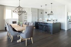 Kelly Deck Design: Open kitchen and dining room floorplan with a trestle dining table and tufted upholstered chairs