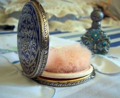 Vintage compact with powder screen and pink puff.