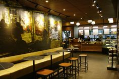 This Starbucks store in Seattle's Belltown neighborhood honors the Art Deco architecture of the existing City University building and features a community table with lots of power outlets so that their students can plug in and keep studying. A custom mural by local artist Mike Martinez makes it look like you're sitting on the Seattle monorail, which runs right next to the store. starbuck store, starbucks stores, thing starbuck, starbucks store design