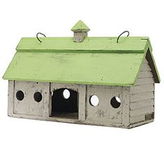 A rustic stable barn shaped birdhouse with a green roof.