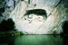 """Etched into a sheer rock wall in Lucerne, Switzerland, a lion, mortally wounded from a spear, lays peacefully in a cavern, life draining from his pained body. Swiss guards died gallantly defending the French royal family in the Bastille uprising. An officer in the guard was home in Switzerland on leave when the riot occurred. Some years later he built this moving monument in honour of his lost comrades marking it Helvetiorum Fidei ac Virtuti (""""To the loyalty and bravery of the Swiss"""")."""