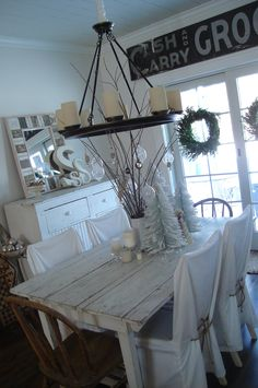 i kinda like this dining room but the white would NEVER work at my house. Love the sign above the window....