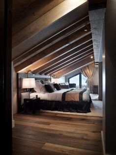 Who says an attic room with a vaulted ceiling has to feel cramped? A dark wood finish changes everything. #flooring #wood #bedroom