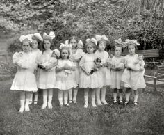 Girls with huge matching hair bows shown holding their dolls, including many German Character Babies, circa 1915.