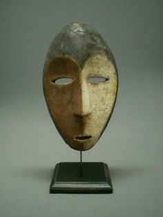 """Lega masks are simple in design yet distinctive in appearance. This mask is 2 tone with red and white pigment. The mask has been mounted on a wood stand with an iron post. The overall height on the stand is 12 1/2""""."""