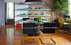 Totalmente integrada à sala, a área do escritório tem prateleiras coloridas. A boa iluminação é garantida pela claridade natural da janela. A mesa de jantar é improvisada com tampo de vidro e três pneus. Projeto do arquiteto Diogo Oliva