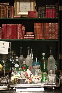 Home bar in a secretary with dark green painted interior, old books
