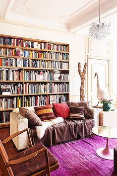 Tour a Belgian Townhouse With Bohemian Flair // bookcase, living room, library, acryclic chandelier, tulip table, kilim pillow