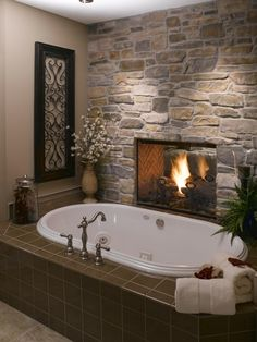 Fireplace between the master bedroom and tub. love