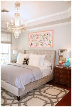 Bedroom with gray walls, white trim, crystal chandelier, modern turquoise lamps, grey velvet upholstered bed, modern art, trellis rug, wood floors, traditional nigshtands. I'd like some more pops of color but love the simplicity.