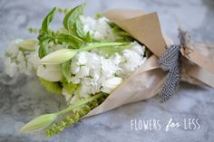 Wrap the flowers in butcher paper and secure with twine. Then attach the tag and stick in the feathers for a final touch.