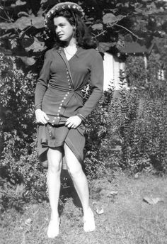 "A young Bettie Page. When she started pin up modeling she didn't have the ubiquitous ""bettie bangs"" as they came to be known.  Somewhere on here I have a photo of her doing a pin up shoot before she got bangs - in bra and undies and not just flashing leg! Looks like she's just warming up to the idea of stripping for the camera in this photo."